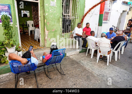 Cartagena Colombia Old Walled City Center centre Getsemani working class neighborhood Hispanic resident residents relaxing man friends playing game si - Stock Image