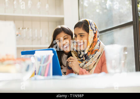 Happy mother in hijab and daughter using laptop - Stock Image