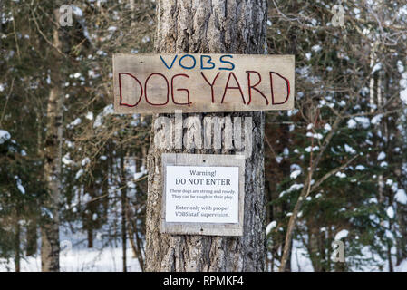 A wooden 'Dog Yard' and 'Do Not Enter' warning signs nailed on a tree. Duluth, Minnesota, USA. - Stock Image