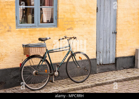 Bicycle at the door of an Aeroskobing home: A utility rocky bicycle stands ready at the door of a yellow brick home in the old town of AEroskobing - Stock Image