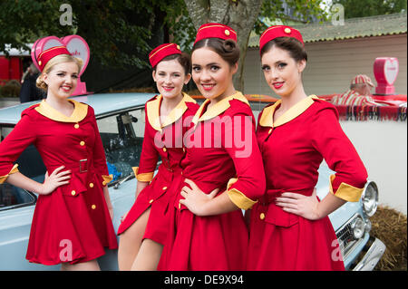 Chichester, West Sussex, UK. 13th Sep, 2013. Goodwood Revival. Goodwood Racing Circuit, West Sussex - Friday 13th September. Glamcabs girls pose for the camera in their red and gold uniforms. © MeonStock/Alamy Live News - Stock Image