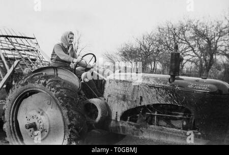 Farmer's wife on the tractor in Wisconsin, ca. 1945. - Stock Image