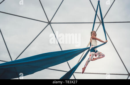 Sport healthy lifestyle people alternative dance in the sky balanced with cords and fabrique - clear white sky in background and steel structure - cir - Stock Image