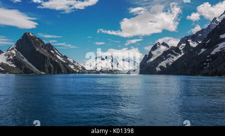 Dramatic scenery of glacial Drygalski Fjord on South Georgia Islands. Steep snow capped mountains beside deep bay. - Stock Image