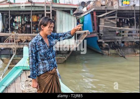 Boatman piloting a tourist vessel on the Irrawaddy River, Mingun Jetty, Mandalay, Myanmar (Burma) - Stock Image