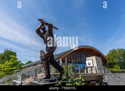 Bronze statue of cricket player Eric Bedser on Bedser Bridge, a footbridge on the Basingstoke Canal linking the WWF-UK headquarters to the town centre - Stock Image