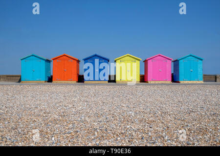 A line of six brightly coloured Beach huts, each one is a different colour in the foreground is a pebble beach and behind is a bright blue sky, Seafor - Stock Image