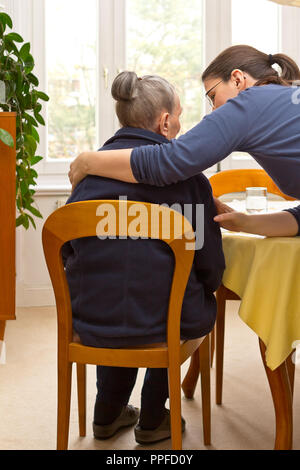 Rear view of a senior woman sitting at home beeing embraced by her granddaughter who is helping her during the day, eldercare by family members - Stock Image