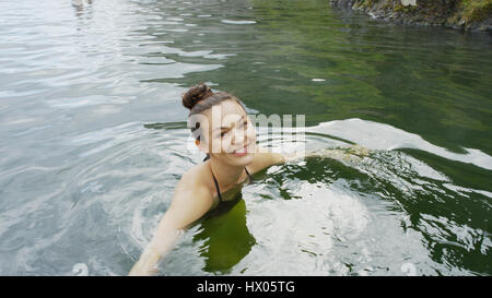 High angle portrait of smiling woman in bikini swimming in remote pool of water - Stock Image
