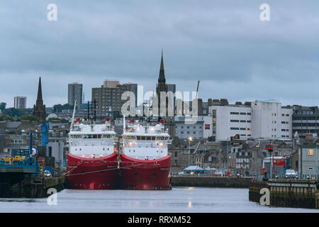 Offshore supply ships in Aberdeen harbour at dusk, Aberdeen, Scotland, UK - Stock Image