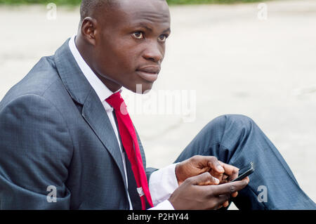 Portrait of young man sitting outside and manipulating his mobile phone - Stock Image