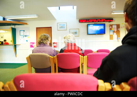 Elderly ill patients sit in a GP surgery waiting room, waiting to be seen by the doctor or nurse - Stock Image