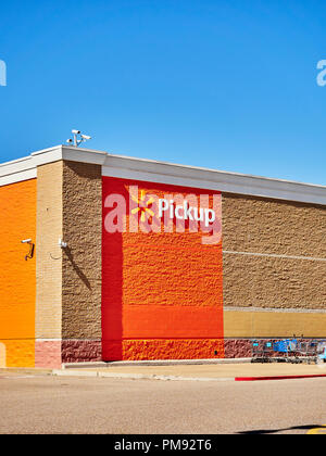 Walmart pickup sign and corporate logo on exterior wall of a super Walmart store in Montgomery Alabama, USA. - Stock Image