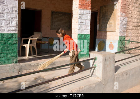 A young Bishnoi schoolgirl sweeps outside her village school before lessons begin - Stock Image