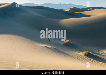 Nude woman in desert running up dune - Stock Image