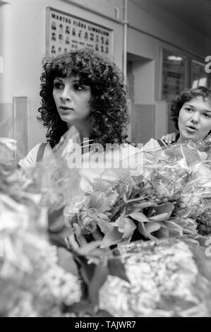 teenage schoolgirl carrying a large bouquet of flowers at school on her graduation day 1970s hungary - Stock Image