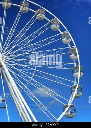 The right hand side of a rotating Ferris Wheel. Blue Sky, Sunshine & fairground rides - it's holiday time! Photo Credit -© COLIN HOSKINS. - Stock Image