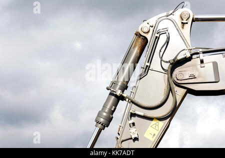 Black hydraulic arm of a digger excavator earthmoving machine with a sky background - Stock Image