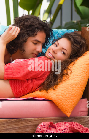 Young couple lying on a couch and romancing - Stock Image