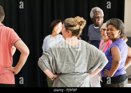 Smiling active seniors exercising in circle - Stock Image
