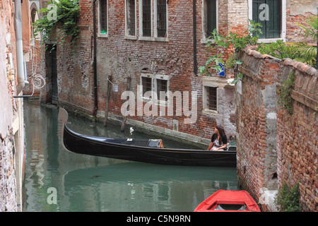 Gondola ride at canal in Venice, Italy - Stock Image
