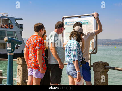 SIRMIONE, LAKE GARDA, ITALY - SEPTEMBER 2018: Family members checking the ferry timetable at the harbour in Sirmione on Lake Garda. - Stock Image