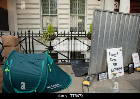 London, UK. 17th June 2019. Richard Ratcliffe on hunger strike in front of the Iranian embassy in London in protest of the detention of his wife Nazanin Zgahari in Iran over spying allegations. A builder has started work on the iron fence and large boxes have appeared from the basement of the embassy, forcing Richard to move his tent forwards, reducing his space on the pavement. Credit: Joe Kuis / Alamy - Stock Image