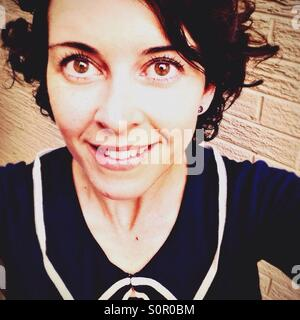 Smiling brunette woman in her thirties with brown eyes - Stock Image
