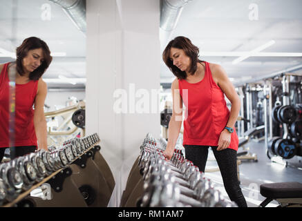 A female senior in gym doing exercise with dumbbells. - Stock Image