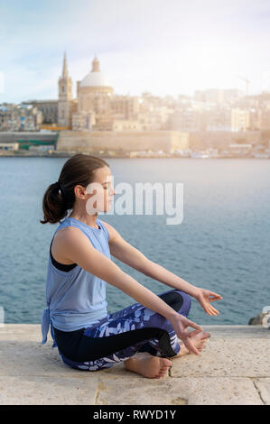 side view of a woman meditating, practicing yoga with Valletta, malta as a backdrop - Stock Image