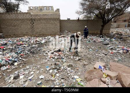 Sanaa, Yemen. 24th Apr, 2019. Street cleaners remove garbage from an area which is most affected by the cholera epidemic, in Sanaa, Yemen, on April 24, 2019. Yemeni street cleaners clean streets and areas which are most affected by the cholera epidemic amid fears of increasing cholera-infected cases in the coming rainy days. Credit: Mohammed Mohammed/Xinhua/Alamy Live News - Stock Image