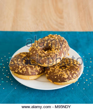 Fresh chocolate caramel donuts on a white plate in soft focus - Stock Image