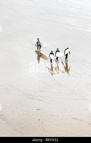 An overhead view of surfers and their surfing instructor carrying their surfboards after a surfing lesson in Newquay in Cornwall. - Stock Image