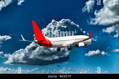 A passenger jet aircraft flyng in a vibrant blue sky, with well developed bright white coloured cumulonimbus clouds, closeup view. - Stock Image