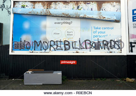 Advertisement billboard defaced with graffiti relating to consumerism, and a dumped fridge below on the pavement. Bristol, UK. - Stock Image