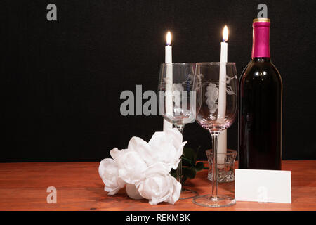 Beautiful etched wine glasses and bottle of red wine, white candles and white roses on wooden table with name tag on dark background. Valentines, Moth - Stock Image