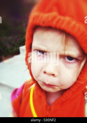 Unhappy child dresses in pumpkin Halloween costume. - Stock Image