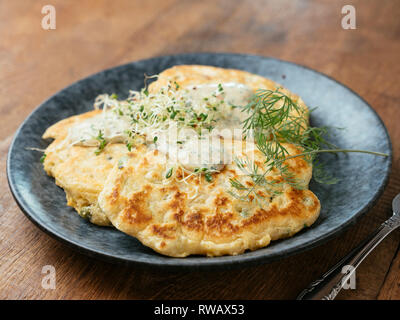Savory vegan pea pancakes with a chives and herbed sauce. - Stock Image