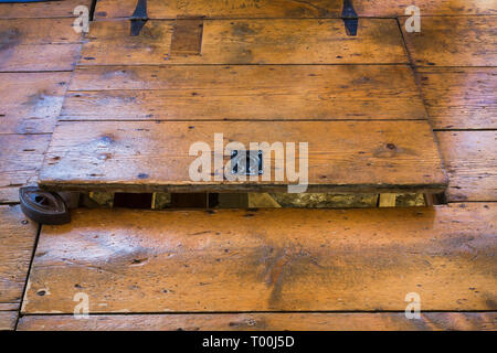 Partially opened hemlock wood plank trap door in dining room leading to crawlspace inside an old circa 1760 Canadiana fieldstone cottage style house - Stock Image