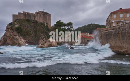 Fort Lovrijenac in Dubrovnic as seen from the beach on a stormy day, with crashing waves and dark clouds. - Stock Image