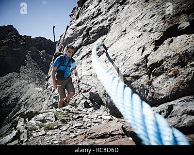 Hiker using rope to ascend rock face, Mont Cervin, Matterhorn, Valais, Switzerland - Stock Image