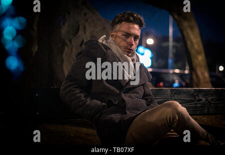 Handsome trendy young man, sitting on bench at night - Stock Image