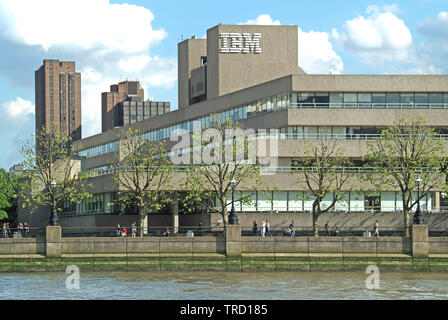 Concrete brutalist architecture & logo of IBM Southbank building people on riverside embankment seen in spring from River Thames London England UK - Stock Image