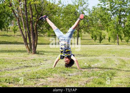 Athletic young boy practicing hand stands in the park balancing with his legs apart amongst spring trees - Stock Image