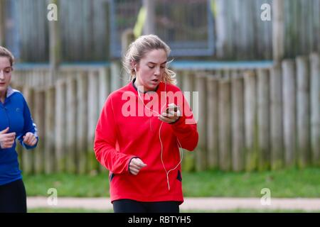 Hastings, East Sussex, UK. 12 Jan, 2019. UK Weather: Winter weather with a slight breeze in the air that is expected to last throughout the day as a few people take a morning stroll around Alexandra park in the heart of Hastings in East Sussex. A young woman looks at her mobile phone while running round the park. © Paul Lawrenson 2018, Photo Credit: Paul Lawrenson / Alamy Live News - Stock Image