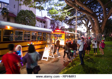 People unloading from chartered school buses parked on roadside to see the Honolulu City Christmas Lights, Honolulu, Oahu, Hawaii, USA - Stock Image