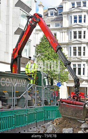 Conway contractor business tipper lorry truck driver loading debris from road & street works excavation with hydraulic grab crane London England UK - Stock Image