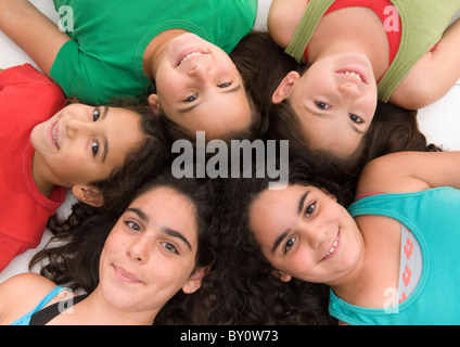 group of five girls heads together isolated on white. - Stock Image