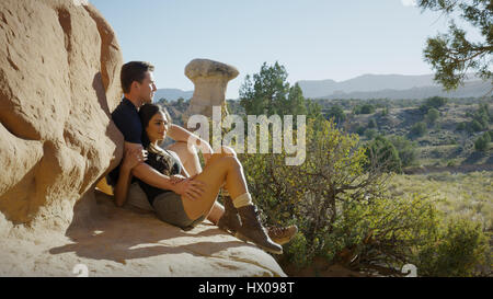 Boyfriend and girlfriend sitting on rocky cliff admiring scenic view of rock formations and trees in remote desert - Stock Image