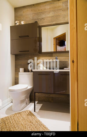 Brown wooden cabinets and bowl sink, tan weaved knotted rug in guest bathroom inside a piece sur piece Eastern white pine log and timber home - Stock Image